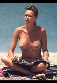 Esther Arroyo sitting topless on a beach