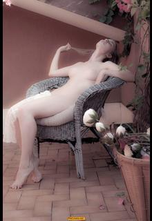 Claudia Lion sitting naked in an armchair